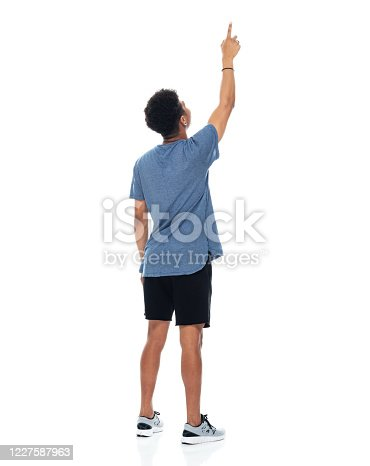 Full length of aged 18-19 years old with curly hair african ethnicity teenage boys standing in front of white background wearing t-shirt who is pointing