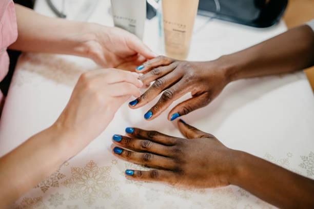 afrikaner frau im spa maniküre von professionellen kosmetikerin erhalten - nägel lackieren stock-fotos und bilder