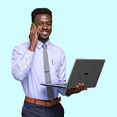 istock African ethnicity young male businessman standing in front of blue background and using computer 1209148842