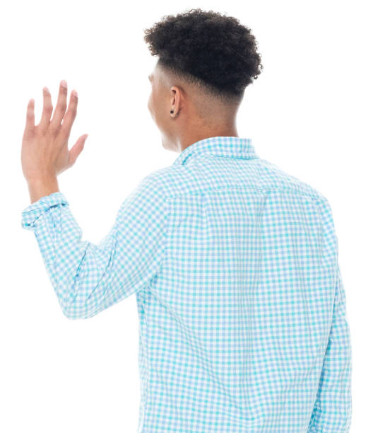 African ethnicity young male standing in front of white background wearing button down shirt stock photo