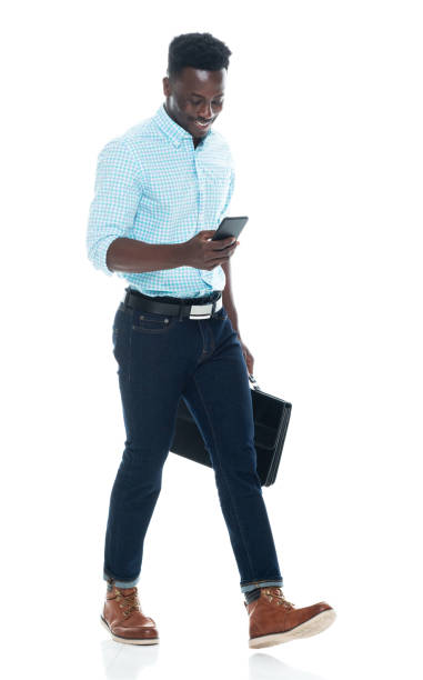 African ethnicity young male walking in front of white background wearing shirt and holding briefcase and using smart phone stock photo