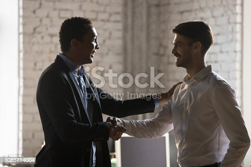 923041456 istock photo African executive manager handshaking caucasian employee promoting praising worker 1085714004