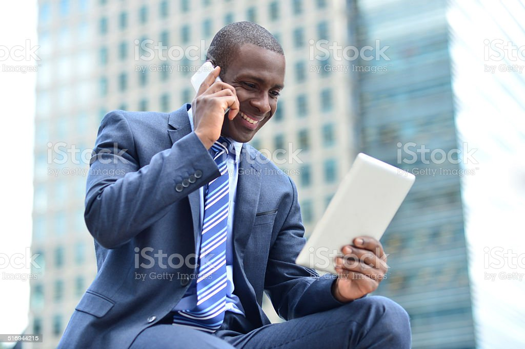 African executive with tablet pc and cellphone stock photo
