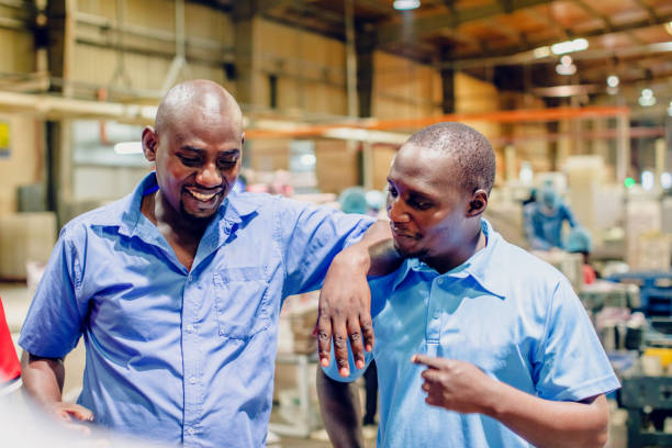 African Factory Supervisor Casually Chatting During their Break Factory, Manual Worker, Quality Control - Factory Supervisors Standing Casually and talking during their break labor union stock pictures, royalty-free photos & images