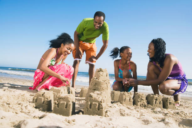 African family building sand castles stock photo