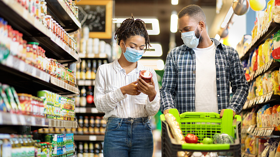 African Family Couple In Shop Buying Groceries Wearing Face Mask Choosing Food Goods Walking With Shopping Cart In Supermarket Store. Customers Buy Essentials During Pandemic. Panorama, Free Space