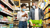 istock African Family In Shop Buying Groceries Wearing Face Masks, Panorama 1287825479