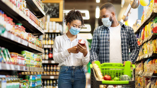 African Family In Shop Buying Groceries Wearing Face Masks, Panorama stock photo
