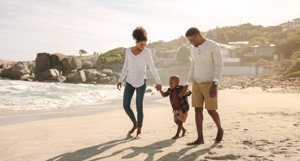 African family on beach walk stock photo