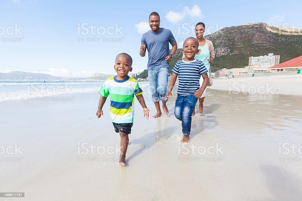 Famille africaine courir à travers la mer le long de la côte - Photo