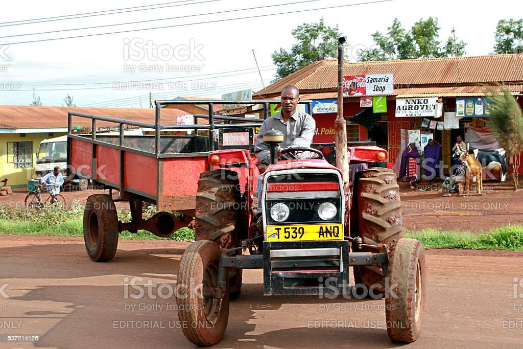 African farmer drives a tractor with a trailer bodywork. stock photo