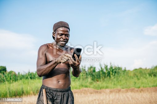 african mid-adult farmer looking on mobile at field  in Malawi