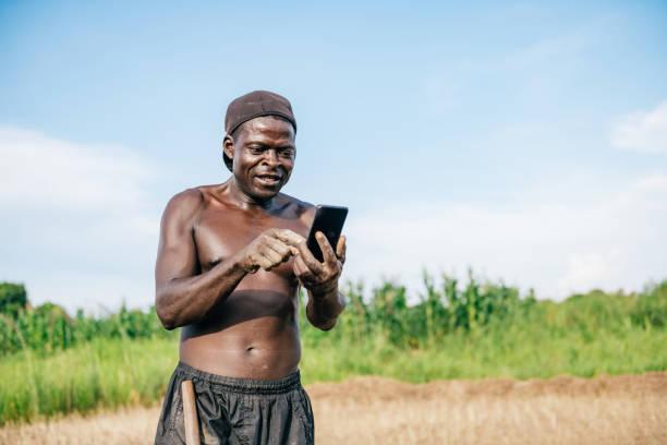 Afrikanischer Landwirt sucht mobil auf Feld – Foto