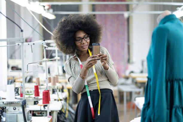 Afrikanische Mode-Designer neue Produkte im Werk erstellen und verwenden von Smartphone – Foto