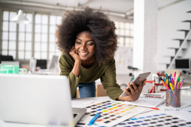 African Fashion designer working in studio and using laptop and smart phone Fashion designer working in studio. Young black woman in an office smiling to camera, close up design professional stock pictures, royalty-free photos & images