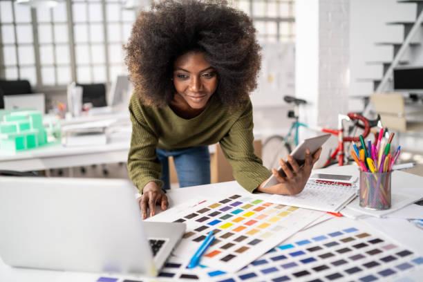 créateur africain de mode travaillant dans le studio et utilisant l'ordinateur portatif et le téléphone intelligent - graphisme photos et images de collection