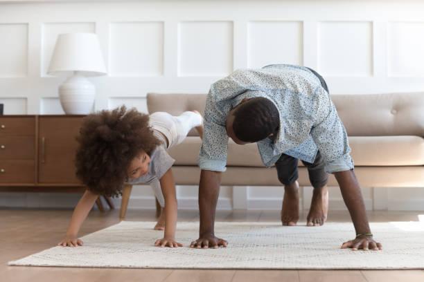 Afrikanischer Vater und kleine Tochter machen Push-up-Übung in Innenräumen – Foto