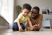 Black dad little son collect jigsaw puzzle put together pieces on warm floor in living room. Leisure activity have fun at home, logical reasoning ability, develop solving and fine motor skill concept