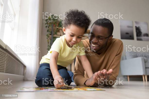 African father and little son collect jigsaw puzzle at home picture id1153592554?b=1&k=6&m=1153592554&s=612x612&h=3mu2lkuelpqc0gcz93x0ap8gog5uj42avoqvvpo vuw=