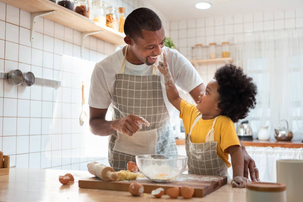 African Father and son enjoying during bake cookies at home together. stock photo