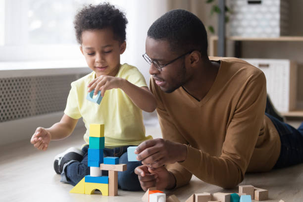 African father and son play with colourful toy blocks Little african boy building tower use colourful toy blocks set sitting on wooden warm heated floor in playroom with daddy or babysitter man, educational game, family at home leisure activities concept one parent stock pictures, royalty-free photos & images