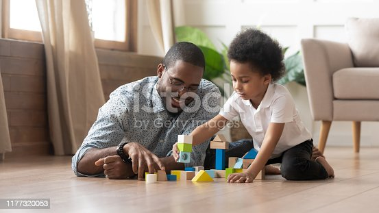 Mixed race young father and small adorable sweet son having fun at modern apartment living room play holding colorful toy blocks set lying sitting on wooden warm floor, family activity at home concept