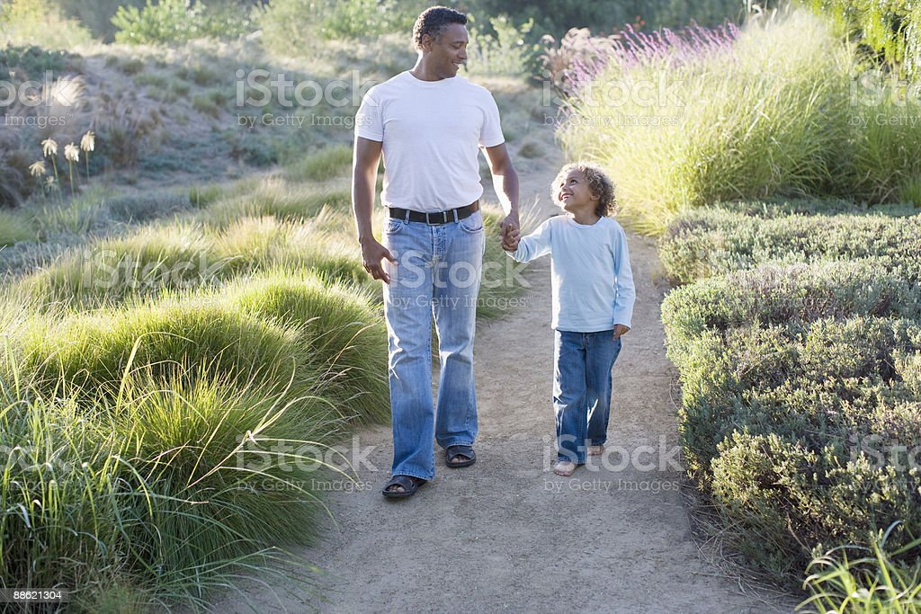 African father and son walking in garden royalty-free stock photo