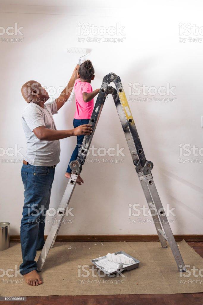 Afrikanischen Vater Hilft Madchen Stehen Auf Leiter An Die Wand