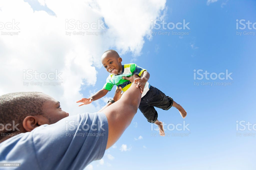 African father holds his son high in the sky stock photo