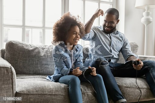 African ethnicity father spend time with little daughter, family sit on couch holding joypads competing in playstation video games, dad loses excited kid girl win. Weekend activity, free time concept