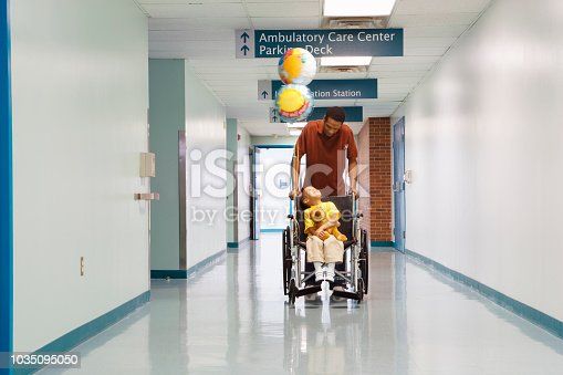 African father pushing son in wheelchair down hospital corridor