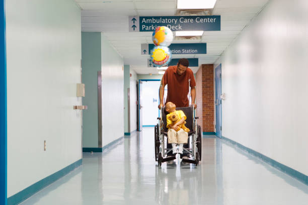 African father pushing son in wheelchair down hospital corridor stock photo