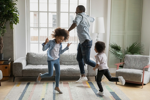 Active african funny dad little son and crazy daughter heavy metal or rock and roll lovers dancing in cozy living room relish life fooling around listening cool music scream with joy enjoy party hard