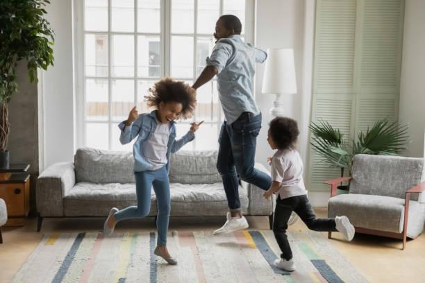 pai africano filho e filha ouvindo música dançando em casa - dançar - fotografias e filmes do acervo