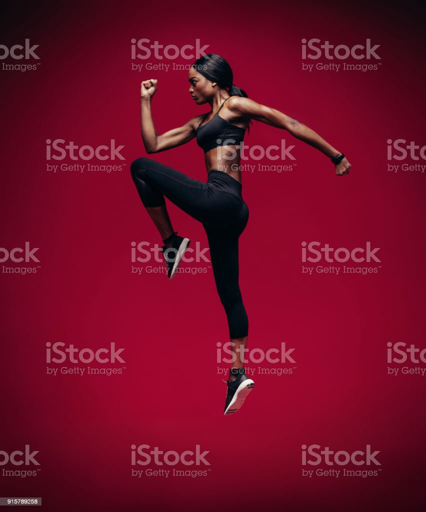 African female athlete jumping and stretching stock photo