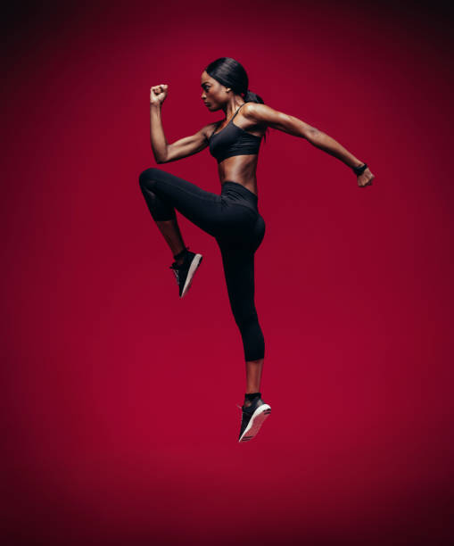 african female athlete jumping and stretching - carpet runner stock photos and pictures