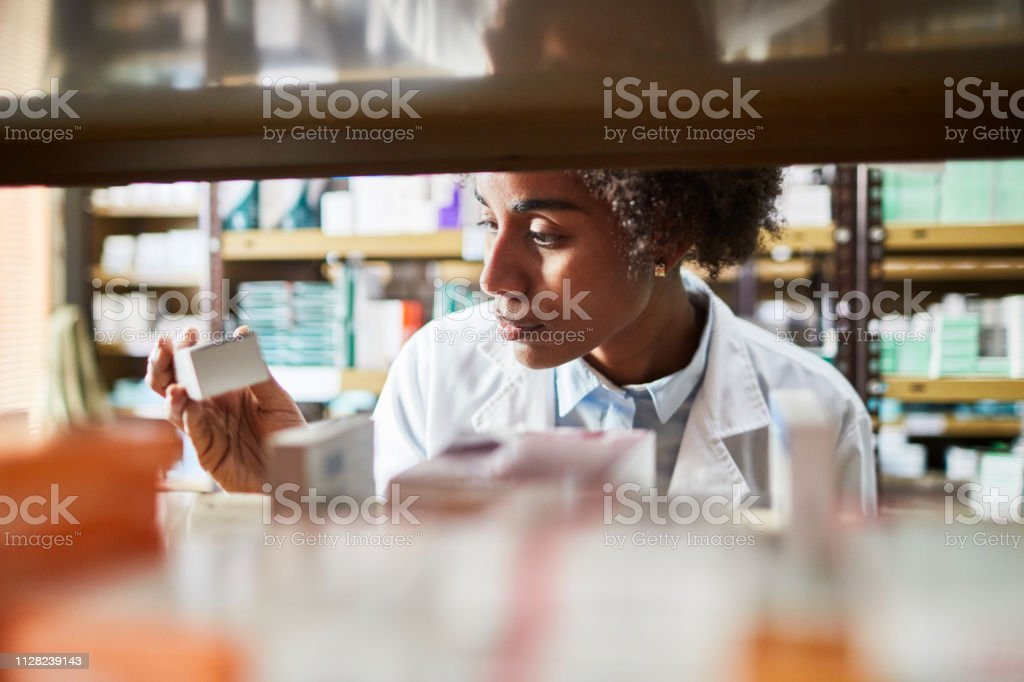 African female chemist searching the medicines stock photo