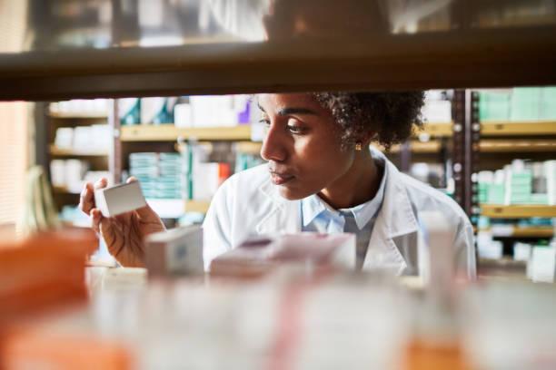 afrikansk kvinnlig kemist som söker medicinerna - sjukvårdsrelaterat material bildbanksfoton och bilder