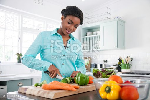 African female in the kitchen chopping a cucumber for her lunch that she's busy preparing. Cape Town, Western Cape, South Africa.