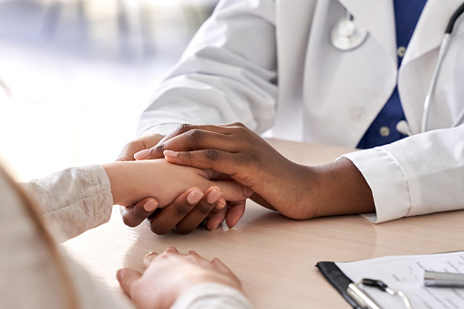 African female doctor hold hand of caucasian woman patient give comfort, express health care sympathy, medical help trust support encourage reassure infertile patient at medical visit, closeup view.