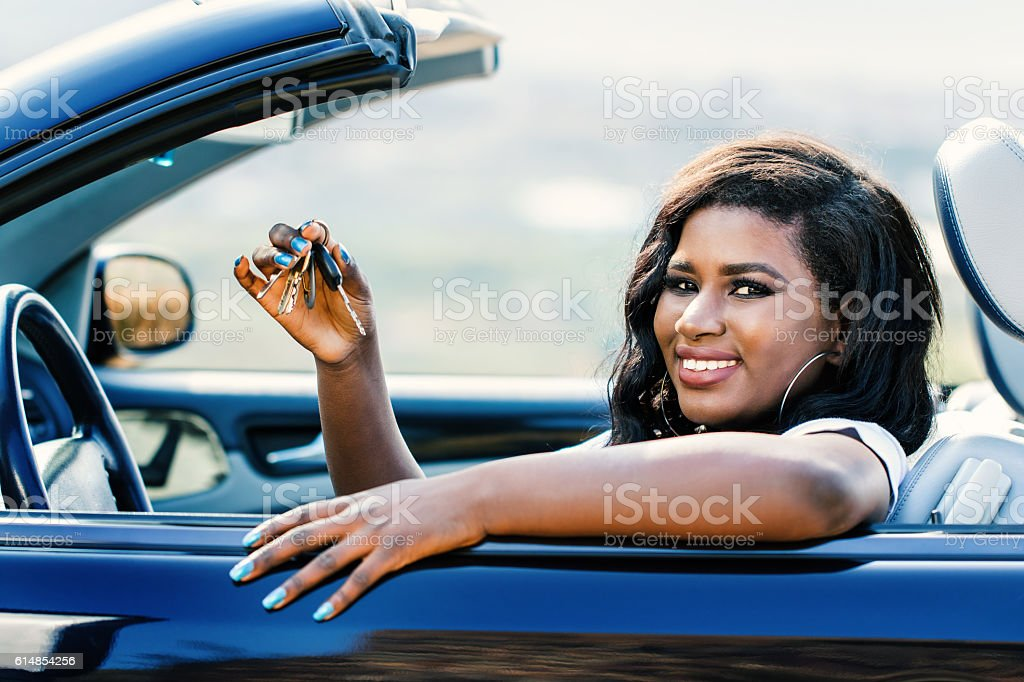 African female driver showing car keys. stock photo