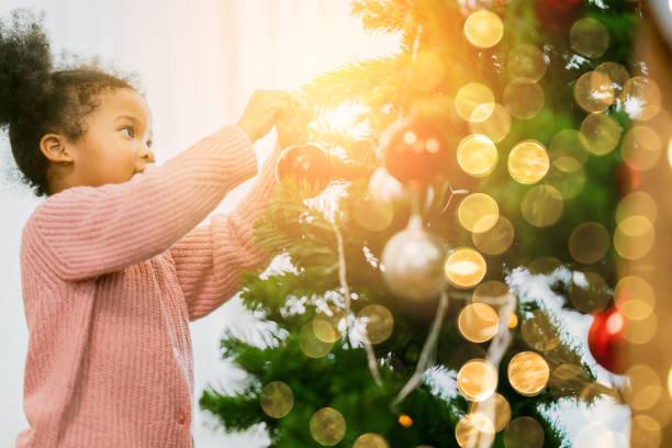 afrikaanse vrouwelijke kid regelen versieren kerstboom met leuke en vrolijke kerst feestelijke ideeën concept - christmas family stockfoto's en -beelden