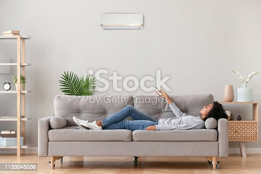 973962328 istock photo African female lying on couch use airconditioner breathing fresh air 1133045036