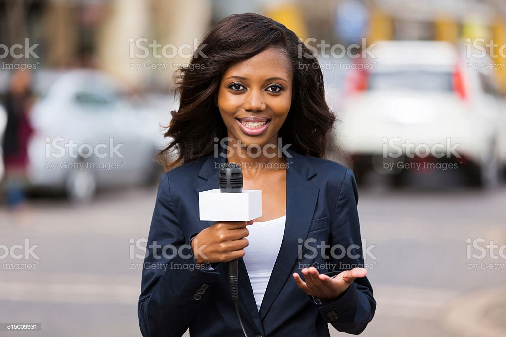 african female news reporter in live broadcasting stock photo