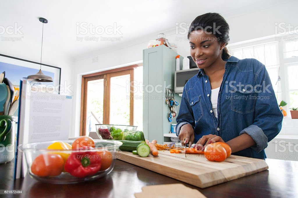 African female peeping the cookbook while chopping carrots. photo libre de droits