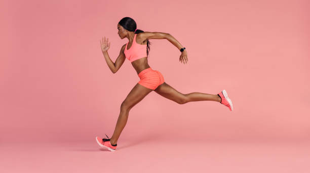 African female runner sprinting stock photo