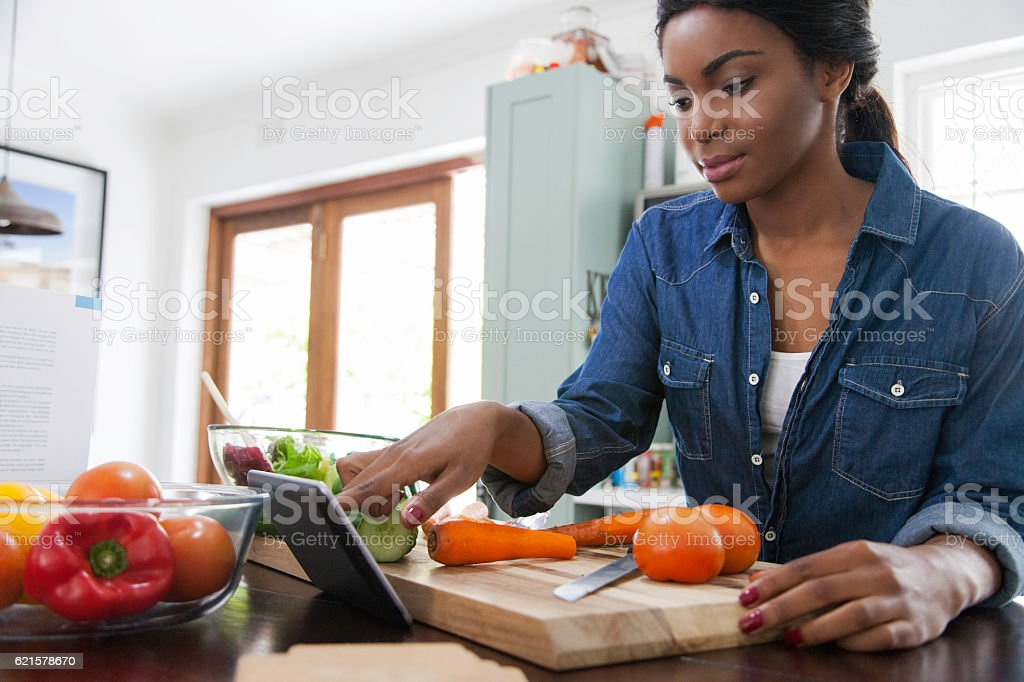 African female scrolling through her digital tablet. stock photo