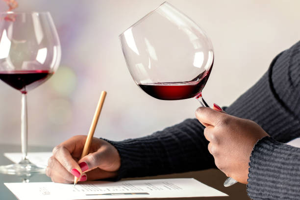 African female sommelier evaluating red wine at table. stock photo