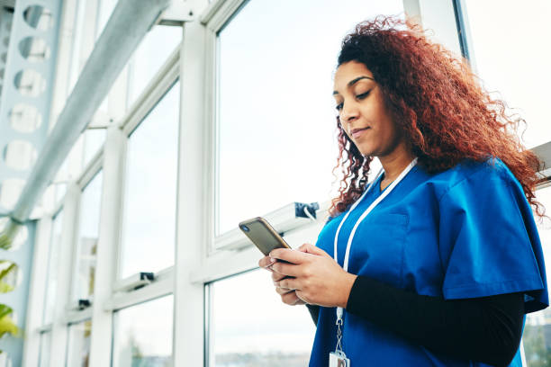african female surgeon using mobile phone - nurse on phone stock photos and pictures
