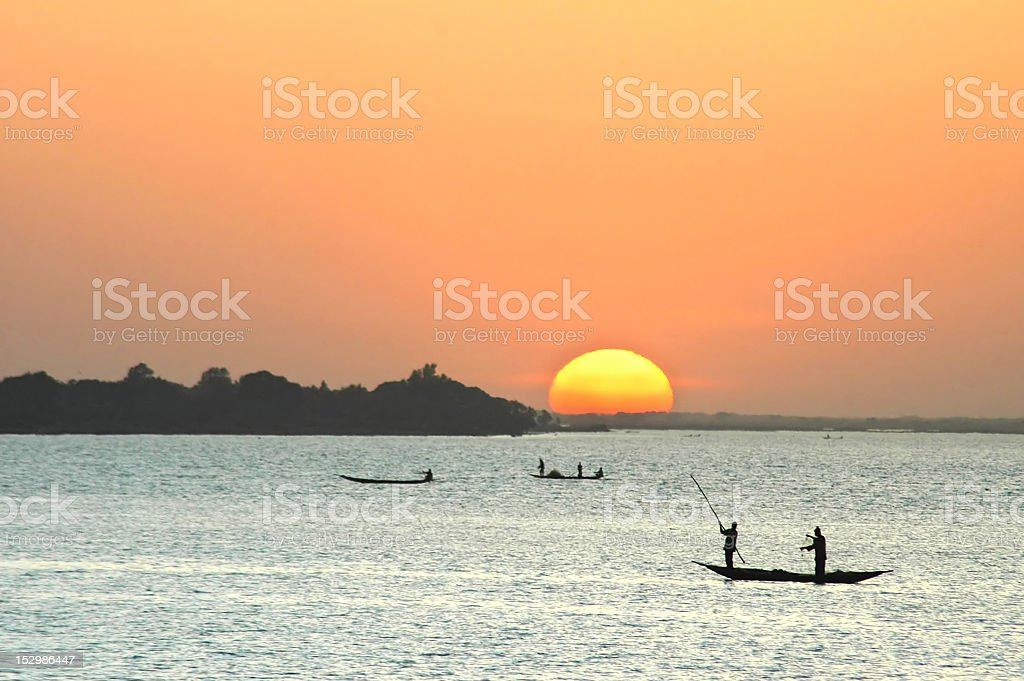 African fishermen in canoes at sunset stock photo